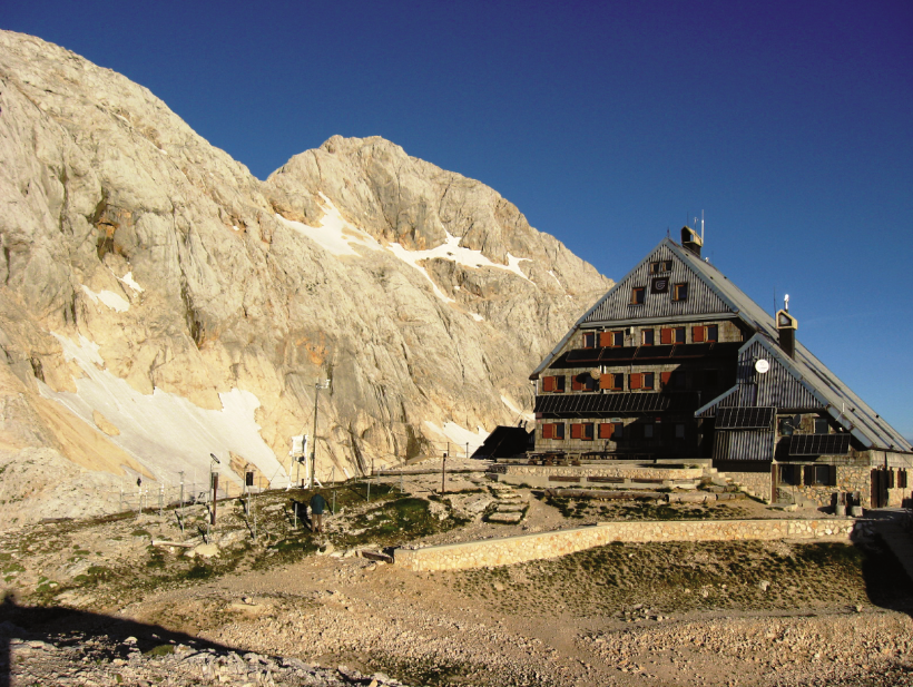 Triglavski dom na Kredarici danes. V ozadju Mali Triglav in glavni vrh ter sloviti greben med njima.