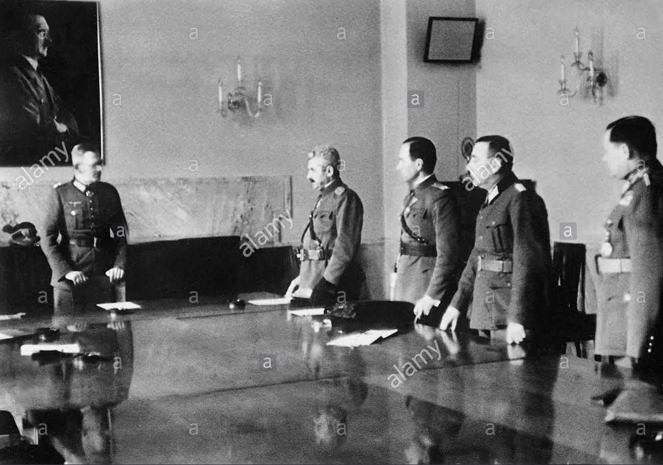 """Weichsova pogajalska miza. Na desni strani stoji jugoslovanska delegacija (z leve proti desni: Bodi in Trojanović), ki posluša mirovne zahteve nemškega tiskovnega predstavnika. Na levi strani fotografije pod portretom Adolfa Hitlerja se nahaja nemški general in glavni pogajalec Maximilian Freiherr von Weichs. General Mihailo Bodi in podpolkovnik Radmilo Trojanović 16. aprila ponudita """"častno premirje"""", katerega von Weichs odločno zavrne. Kmalu zatem je bilo sestanka tudi uradno konec, še dandanes pa se v nemških in jugoslovanskih arhivih kot znak uradne kapitulacije še vedno pojavlja fotografija z neuspešnega pogajanja 16. aprila 1941. Brezpogojno kapitulacijo sta šele naslednjega dne podpisala Cincar-Marković in Radivoje Janković."""